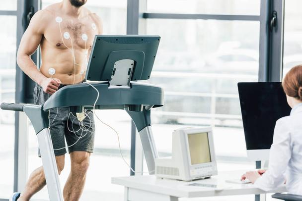partial view of doctor conducting endurance test with sportsman in gym - Photo, Image