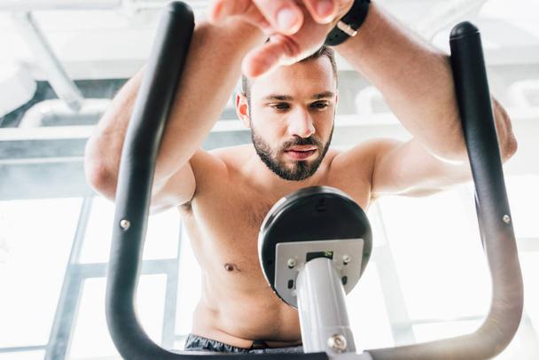 handsome sportsman training on elliptical machine at gym - Photo, Image