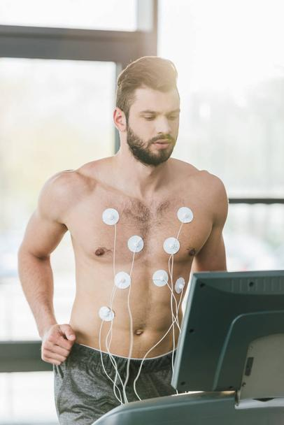 handsome sportsman with electrodes running on treadmill during endurance test in gym with daylight - Photo, Image