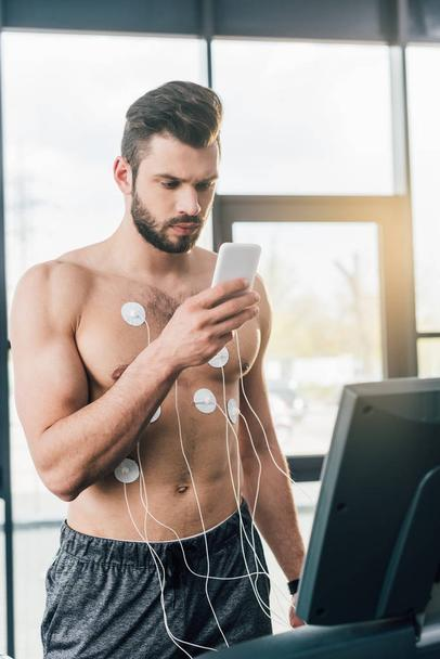 sportsman with smartphone running on treadmill during endurance test in gym - Photo, Image