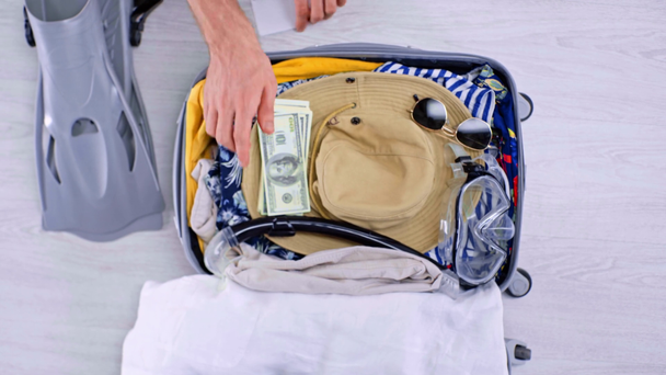 cropped view of man packing summer clothes, swimming accessories, money, passport an air ticket in suitcase on floor at home - Footage, Video