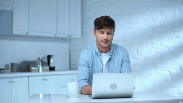 cheerful freelancer using laptop and drinking coffee with smile in kitchen - Footage, Video
