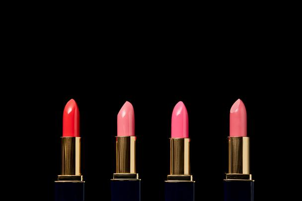 various shades of lipsticks in tubes isolated on black    - Photo, Image