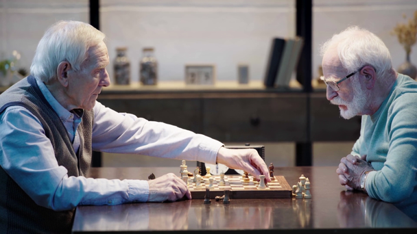 side view of two pensive senior men playing chess and pressing button on chess clock at table - Footage, Video