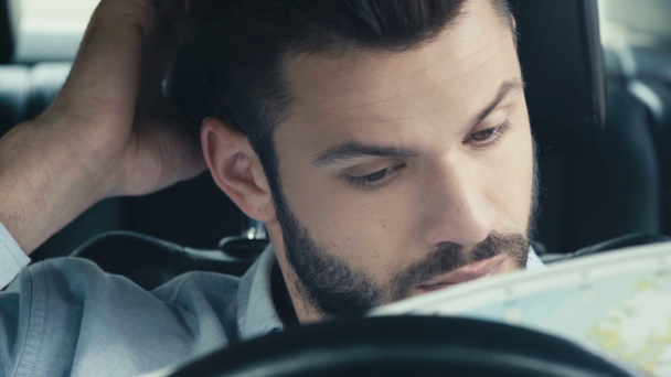selective focus of handsome man taking map, opening and looking while sitting in car  - Footage, Video