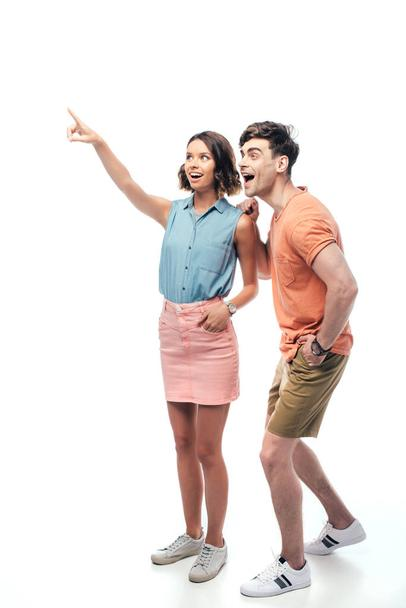 smiling woman pointing with finger and looking away with excited man on white background - Photo, Image