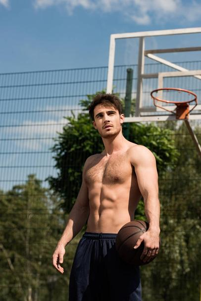 shirtless basketball player with ball at basketball court in sunny day - Photo, Image