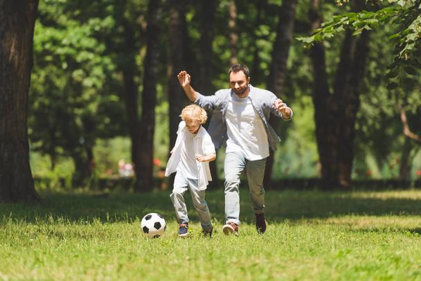 handsome father and adorable son playing football in park - Photo, Image
