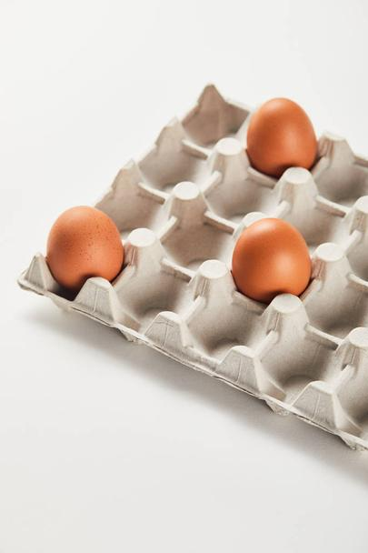 chicken eggs in carton box on white surface - Photo, Image