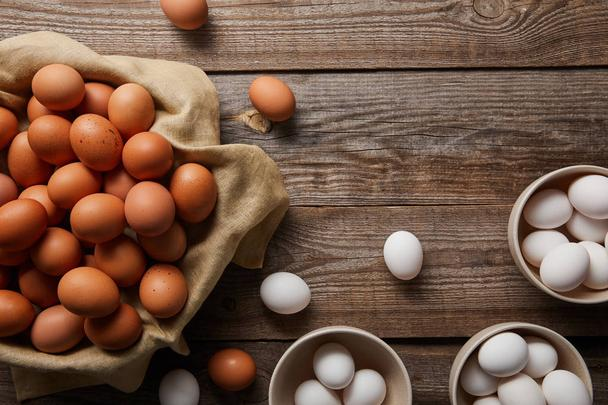 top view of chicken eggs in bowls on wooden table with cloth - Photo, Image