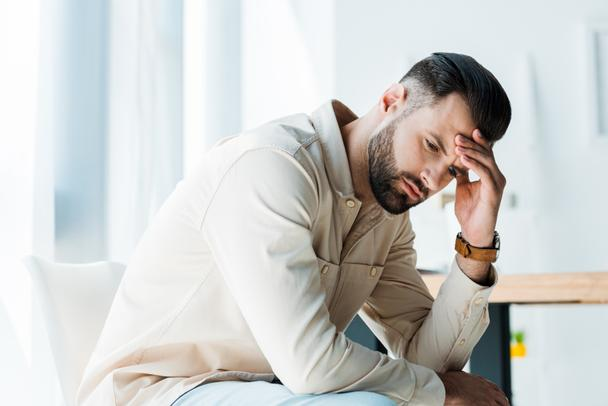 handsome upset man sitting and touching head in office  - Photo, Image