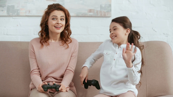 KYIV, UKRAINE -  APRIL 15, 2019: excited kid playing video game with mother, enjoying victory and smiling while mother stroking her head - Footage, Video