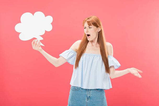 irritated redhead young woman holding empty thought bubble isolated on pink - Photo, Image