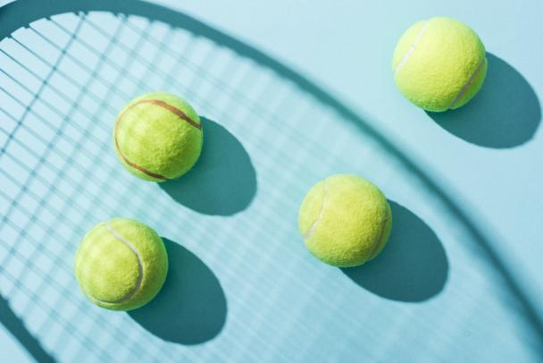 top view of tennis balls near shadow of tennis racket on blue  - Photo, Image