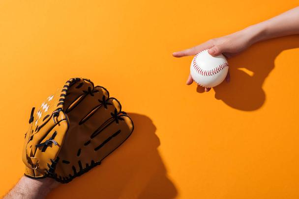 cropped view of man in brown baseball glove near woman holding softball on yellow  - Photo, Image