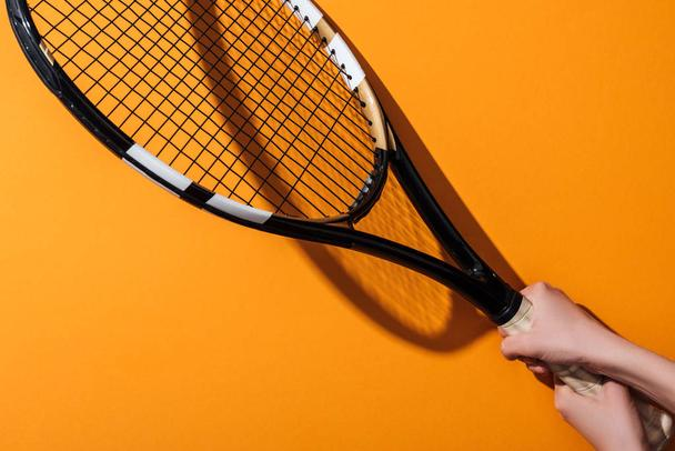 cropped view of sportive woman holding tennis racket on yellow  - Photo, Image