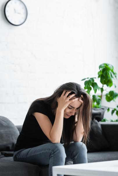 depressed girl crying while sitting on couch at home and holding hands on head - Photo, Image
