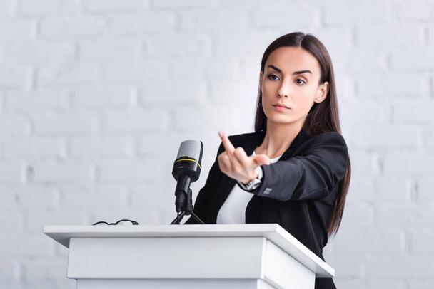 dissatisfied lecturer standing on podium tribune in conference hall and showing middle finger - Photo, Image