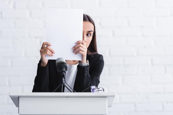 young lecturer suffering from fear of public speaking hiding face with paper sheet while standing on podium tribune - Photo, Image
