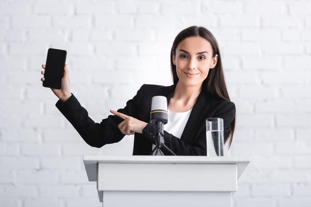 smiling lecturer standing on podium tribune and pointing with finger at smartphone with blank screen - Photo, Image