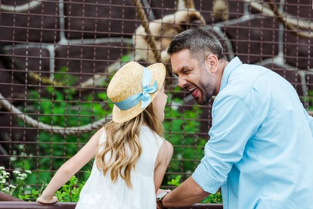 kid in straw hat looking at father showing tongue near cage with wild animal in zoo  - Photo, Image