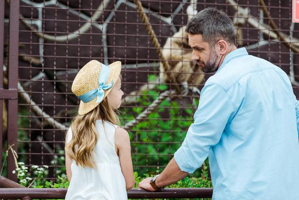 kid in straw hat looking at upset father near cage with wild animal in zoo  - Photo, Image
