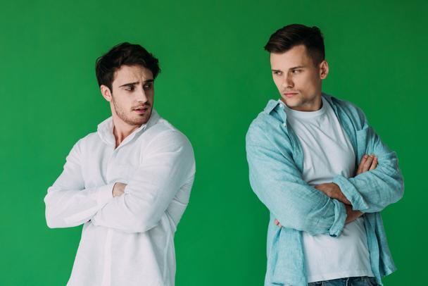 two offended men in shirts standing with crossed arms isolated on green - Photo, Image