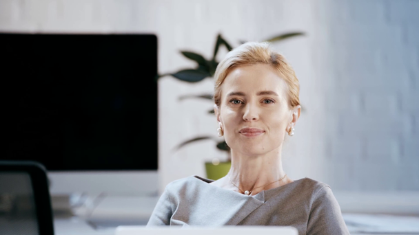 happy businesswoman in formal wear smiling and looking at camera in office  - Footage, Video