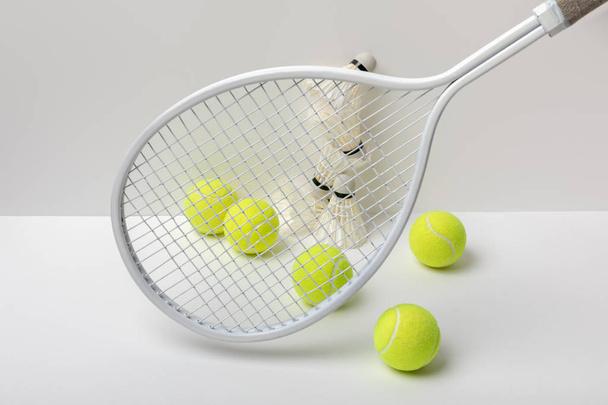 white badminton shuttlecocks and bright yellow tennis balls near racket on white background - Photo, Image