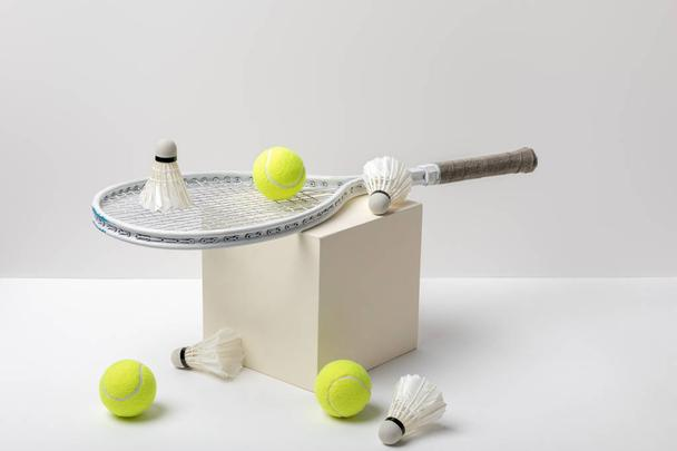 tennis racket and bright yellow tennis balls with shuttlecocks on cube on white background - Photo, Image