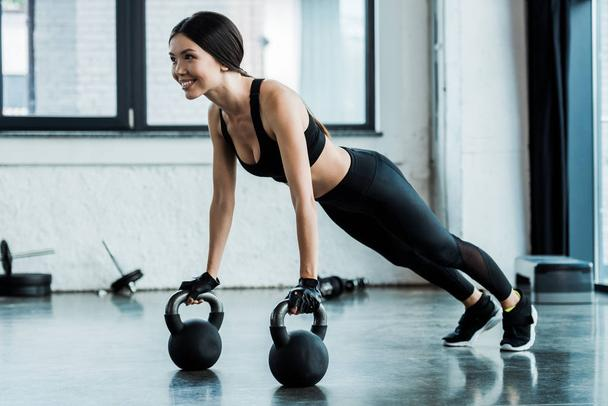 cheerful woman in sportswear exercising with dumbbells  - Photo, Image