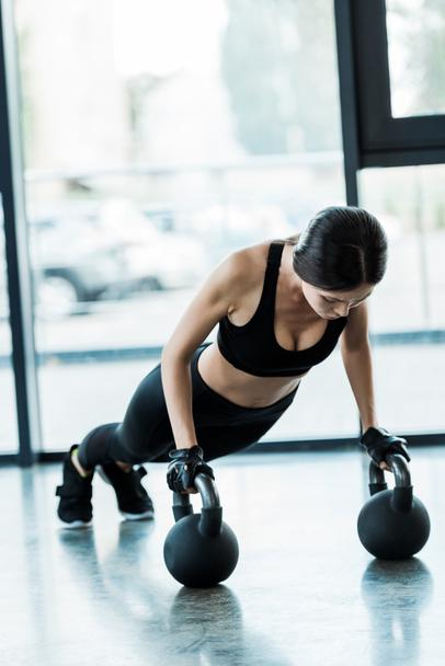 young woman in sportswear exercising with dumbbells  - Photo, Image