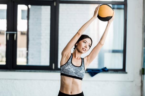 attractive young sportswoman holding ball while working out in gym  - Photo, Image