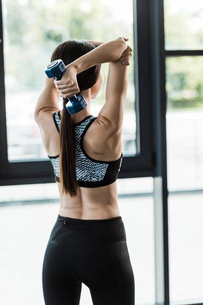 back view of sportswoman working out with dumbbell in gym  - Photo, Image