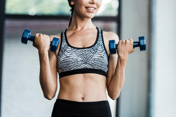 cropped view of cheerful girl holding dumbbells  - Photo, Image