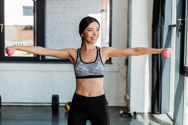 cheerful girl exercising with dumbbells while standing in sports center - Photo, Image