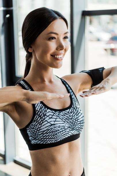 cheerful young athletic woman working out in sports center - Photo, Image