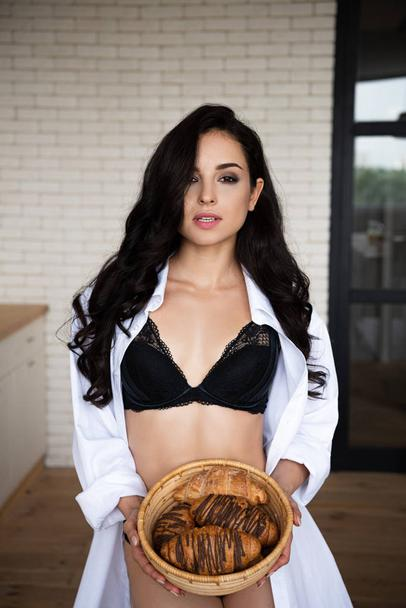 sexy girl in black underwear and white shirt holding basket with buns and looking at camera - Photo, Image