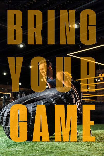 low angle view of athletic bearded man working out with huge car tire on green grass with bring your game illustration - Photo, Image