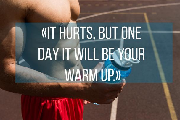 it hurts, but one day it will be your warm up lettering on partial view of shirtless muscular sportsman holding sport bottle - Photo, Image