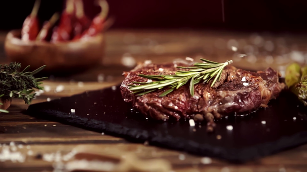 falling salt on delicious meat steak on table with ingredients - Footage, Video