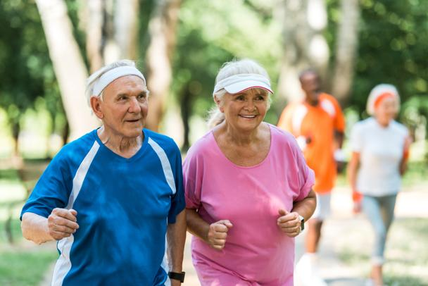 selective focus of happy retired couple exercising outside  - Photo, Image