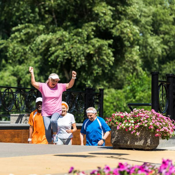 selective focus of cheerful retired woman celebrating triumph near multicultural pensioners in park  - Photo, Image