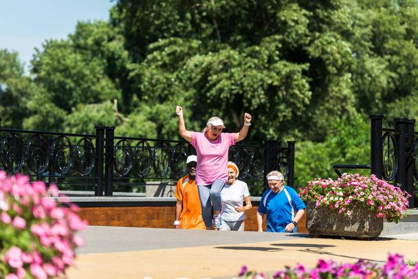 selective focus of happy retired woman celebrating triumph near multicultural pensioners in park  - Photo, Image