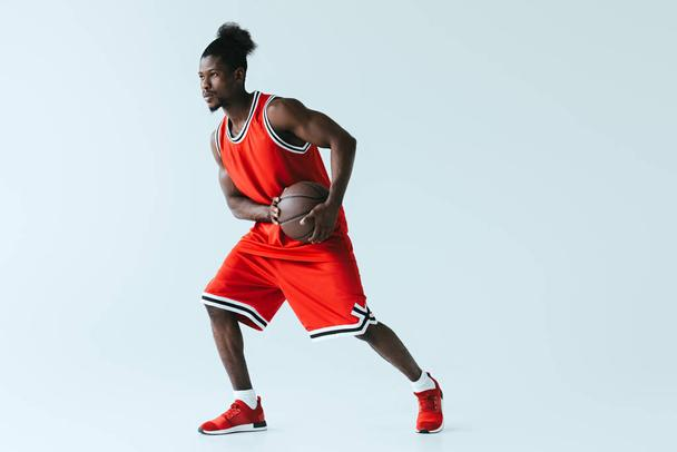 african american basketball player in red sportswear holding ball on grey background - Photo, Image