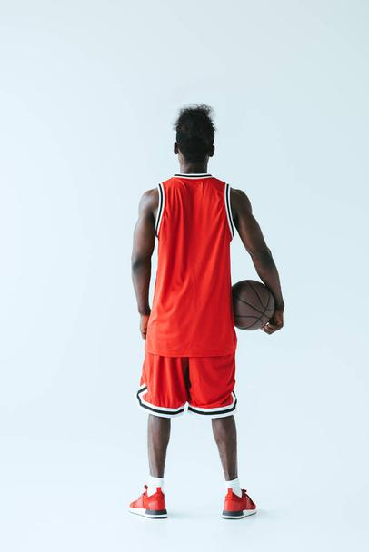 back view of african american basketball player holding ball on grey background - Photo, Image