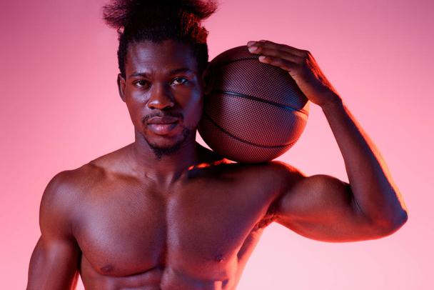confident, shirtless african american basketball player holding ball and looking at camera on pink background with gradient - Photo, Image