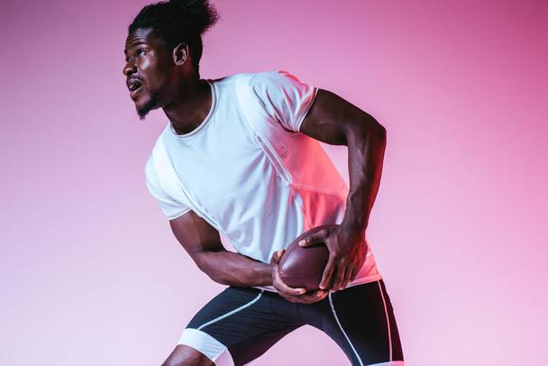excited african american sportsman playing american football on purple background with gradient - Photo, Image
