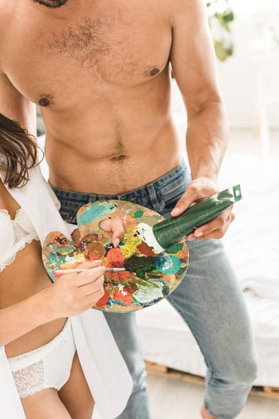 Muscl guy around sexy girls holding them Sexy Girl In White Underwear Holding Brush And Palette While Man Adding Green Paint On Palette Free Stock Photo And Image