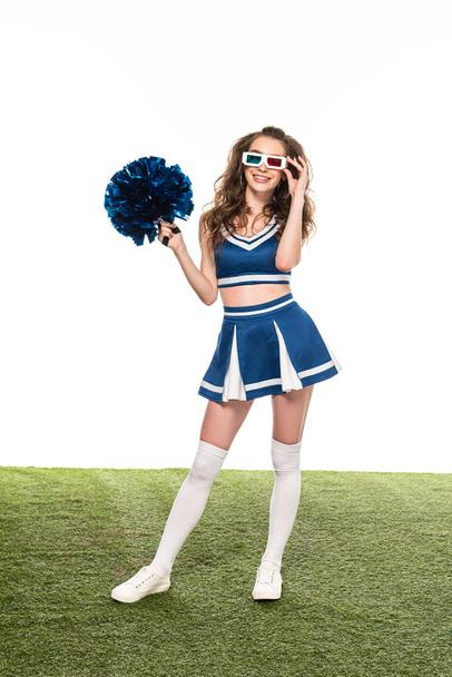 happy cheerleader girl in blue uniform and 3d glasses standing with pompom on green field isolated on white - Photo, Image